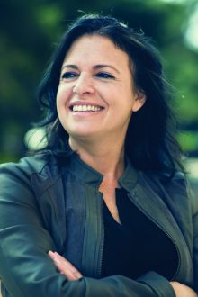 Image of a smiling Jennifer Granick in a green leather jacket.
